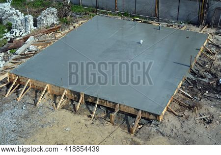 Timber formwork with metal reinforcement for pouring concrete and creating a solid foundation for a building or fence. Construction process