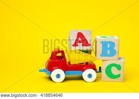 English Letters Abc On Wooden Blocks In A Toy Plastic Truck On A Yellow Background. Learning Foreign