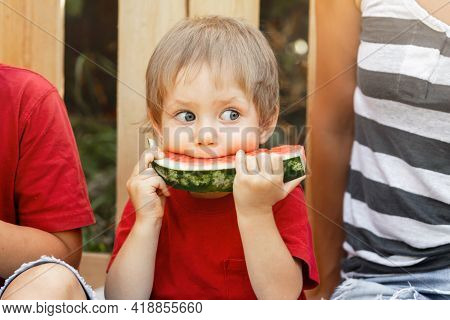 American Kid Enjoy Eating Watermelon During Going For Camping Countryside. Caucasian Boy Enjoying Wa