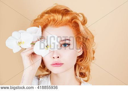 Woman With Beauty Face, Facial Skin Portrait. Coscmetic And Beauty Concept. Woman With Orchid Flower