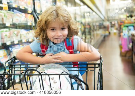 Child With Shopping Basket Purchasing Food In A Grocery Store. Customers Family Buying Products At S