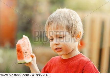 Funny Kid Eating Watermelon Outdoors In Summer Park. Happy Child Eating Watermelon In The Garden. Po