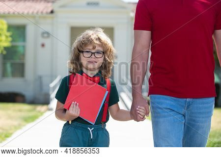 Parent And Nerd Pupil Of Primary School Go Hand In Hand. Father Holding Hand Of Son With Backpack Ou