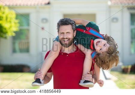 Father Giving Son Piggyback Ride After School Study. Parent And Pupil Of Primary School Schoolboy Wi