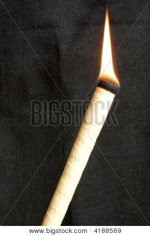 A lighted ear candle against a black background. poster