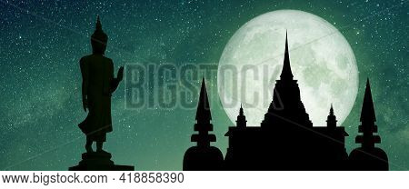 Silhouette Of Buddha Statue And Temple With Full Moon Under The Milky Way At Night.