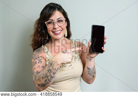 Brazilian Woman Wearing Glasses, Tattooed, Smiling And Pointing Her Finger At Smatphone.