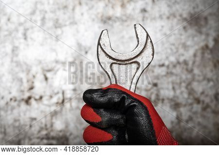 Person wearing protective glove holding big wrench against metal background