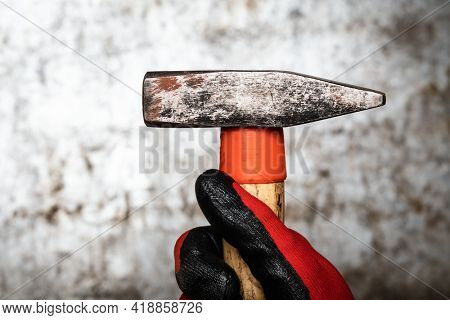 Person wearing protective glove holding a hammer against metal background