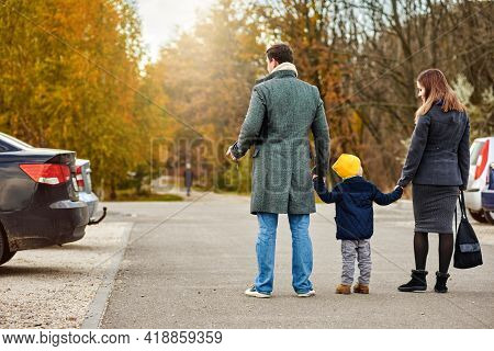 Family Of Three People Walking To Their Parked Car After Stroll In Autumn Park