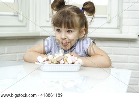 Happy Contented Little Girl Eating Marshmallows From A Plate Full Of Sweets. Child Overeats Sweets.