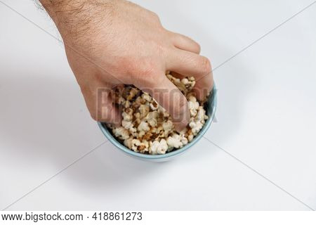 Burnt Popcorn Kernel In Blue Cup, Man's Hand Takes Popcorn