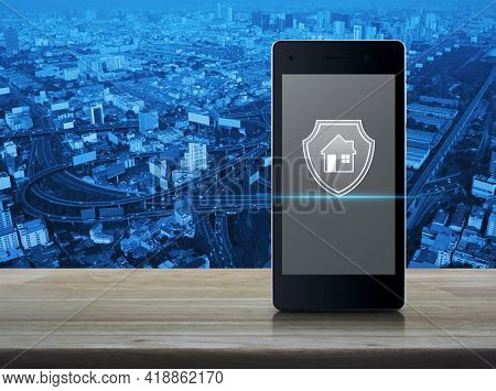 House With Shield Flat Icon On Modern Smart Mobile Phone Screen On Wooden Table Over Office City Tow