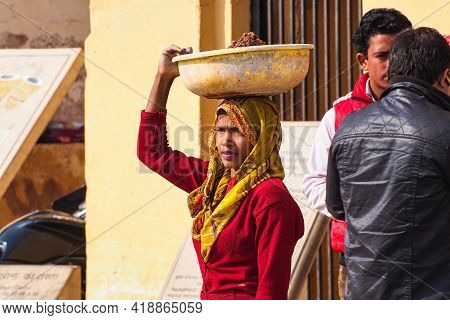 Jaipur, India - Jan 05, 2020: Woman With A Bowl On Her Head Near Amber Fort In Jaipur, India.