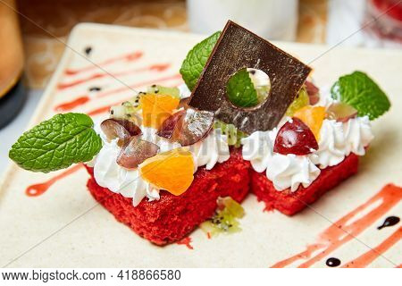 Red Sponge Cake With Fruit, Cream Cheese, Chocolate And Mint Leaves. Close-up, Selective Focus