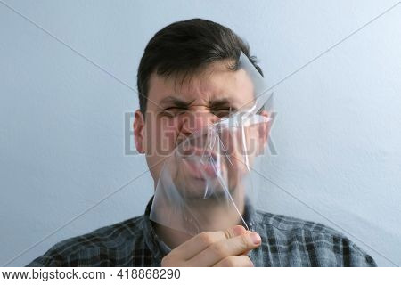 Portrait Of Man Is Puttion On Plastic Transparent Film On His Face.