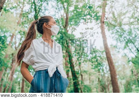 Walking in nature woods wearing face mask during coronavirus pandemic. Asian woman in sustainable eco friendly clothing fashion fabric. People lifestyle sustainability concept.