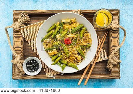 Stir Fry, Thin Rice Noodles With Squid And Okra In A Gray Plate On A Light Blue Concrete Background.