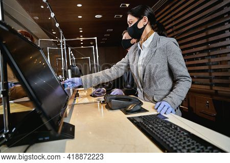 Hotel Receptionists Following The Pandemic Safety Precautions