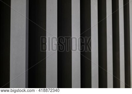 The Background Of Alternating Vertical Columns Of Black And Steel Color In Perspective.