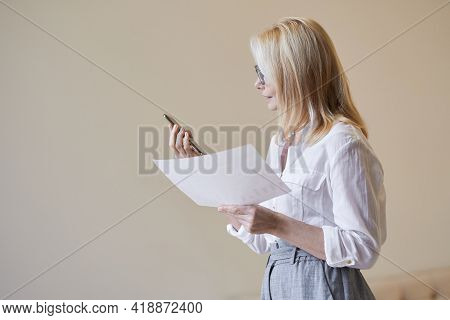 Make Business Happen. Busy Mature Woman With Blonde Hair In Business Attire Holding Her Smartphone A