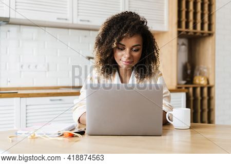 The happy black woman sitting in front of laptop and looking at him in the white kitchen
