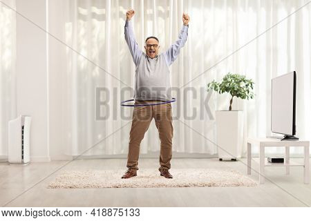 Full length portrait of a happy mature man spinning a hula hoop and lifting arms up in a living room