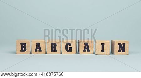 The Word Bargain Made From Wooden Cubes On Blue Background. Conceptual Photo