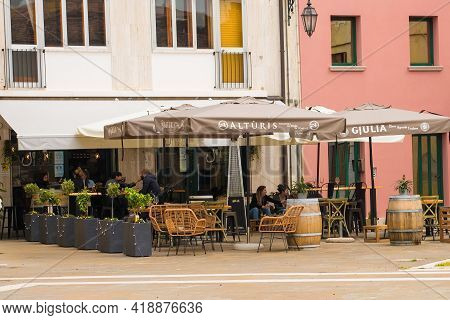 Marano Lagunare, Italy - April 29th 2021. A Bar Serves A Few Lunchtime Customers Willing To Brave Th