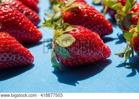 Close Up Of Tasty Red Strawberries With Green Leaves On A Blue Background.healthy Food Concept