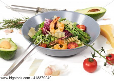 Close Up Of Modern Blue Plate With Vegetables Salad With Pasta, Avocado And Shrimps On White Backgro