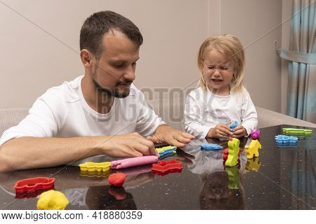 Crying Little Child And Young Caucasian Dad Play With Colorful Play Dough, Making Animals, Upset Exp