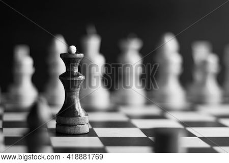 Black Chess Queen On A Background Of White Pieces On A Chessboard, Black And White Photo, Selective