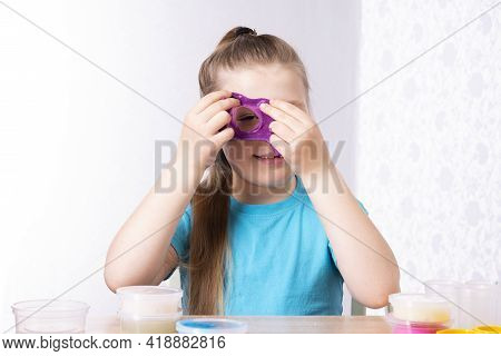 Blonde-haired Little Girl Plays With Slime. Little Beautiful Caucasian Girl Looks Through A Hole In
