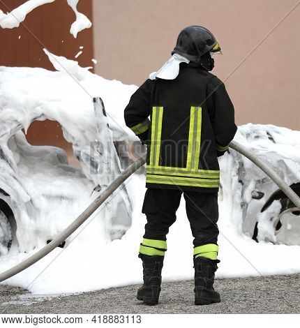 Firefighter Extinguishing A Fire A Car With The Foam After The Car Accident