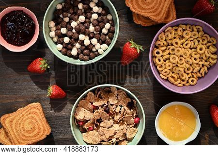 Morning Continental Breakfast Flatlay With Corn Flakes Bowls, Cereals, Honey, Strawberry, Jam, Bread
