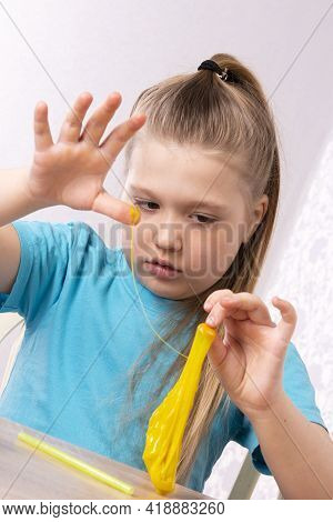 Blond Beautiful Caucasian Young Girl Is Playing With Yellow Slime. Play A Slime Toy. Making Slime At