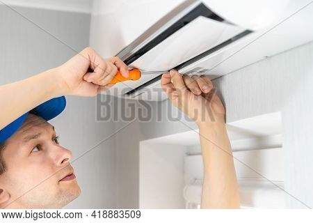 Repairman In Overalls With A Screwdriver In His Hands Repairs An Air Conditioner On The Wall