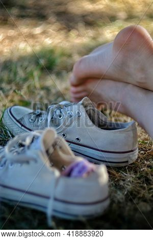 Part Of A Young Woman's  Feet And A Pair Of Sneakers Outdoors In Nature On A Sunny Day In France