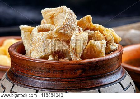 pork rinds (torresmo) on rustic wooden table in restaurant. typical dish of Brazilian and Asian cuisine