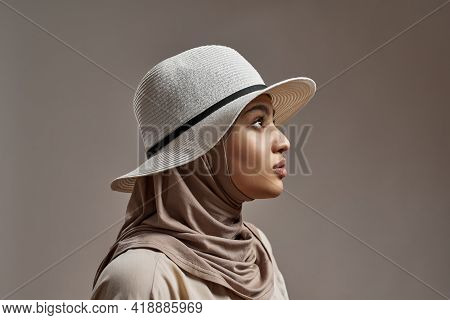 Profile Of Young Arabian Girl In Hijab And Hat Posing On Light Background And Looking To Side. Beaut