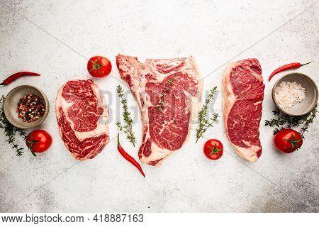 Variety Of Fresh Raw Black Angus Prime Meat Steaks T-bone, New York, Ribeye And Seasoning On White B