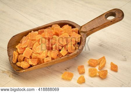 dried mango fruit diced - rustic wooden scoop on a distressed wood background