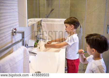 Older Brother Learning To Clean The Teeth For Younger Brother In The Bathroom With Mirror