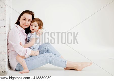 Beautiful Happy Family Sit On Floor And Cuddle In White Photo Studio.