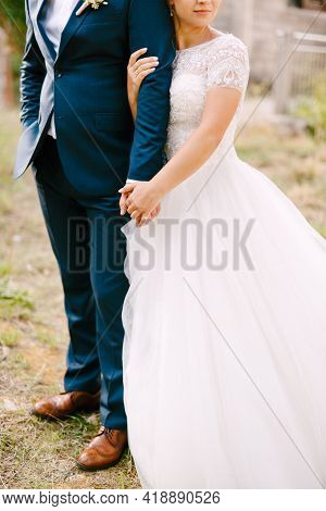 The Bride And Groom Stand Embracing, The Bride Holds The Grooms Hand And Gently Hugs