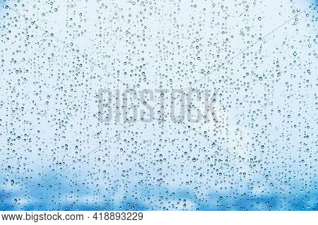 Water Droplets On Glass In Rainy Weather With Small Town Sleeping Areas Out Of Focus In The Backgrou