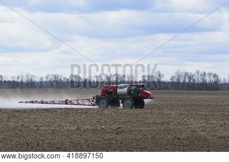 Red Tractor With Irrigation System Watering A Field On A Cloudy Day. Agricultural Machinery, Work In