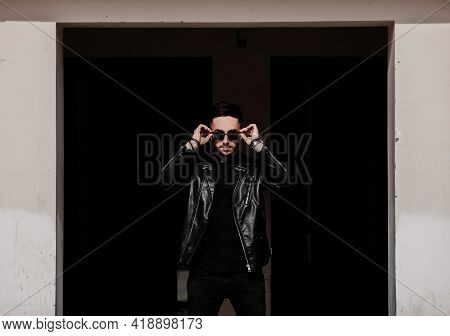 Young Stylish Man Wearing Casual Jacket And Sunglasses In Urban Background.