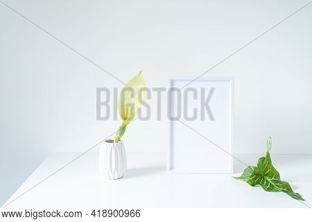 Empty White Frame Mockup On White Table. Modern White Vase With Arum Italicum Flower And Green Leaf.